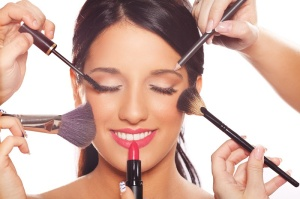 Beautiful young happy fashion model at beauty treatment applying professional makeup. Isolated on whie background